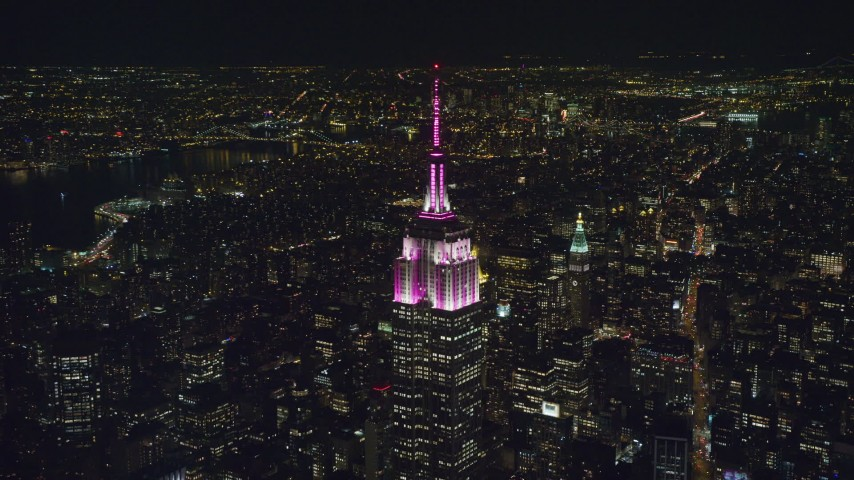 6K aerial video of circling the Empire State Building with striped lights at Nighttime, Midtown, NYC Aerial Stock Footage | AX122_099