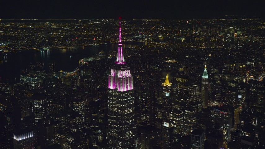 Circle the Empire State Building with Pink and White Lights at Night Aerial Stock Footage | AX122_100