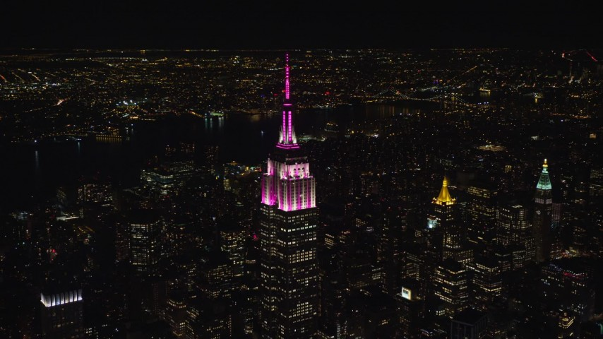 5.5K stock footage aerial video circle the Empire State Building with pink and white lights at Night, Midtown, NYC Aerial Stock Footage | AX122_100E