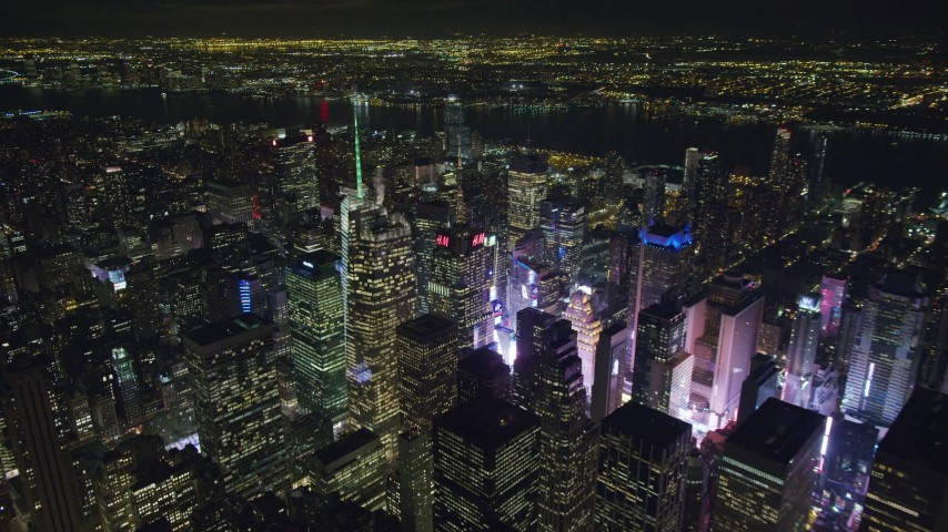 6K stock footage aerial video of circling the Bank of America Tower toward the glow of Times Square at Night, Midtown, NYC Aerial Stock Footage | AX122_115