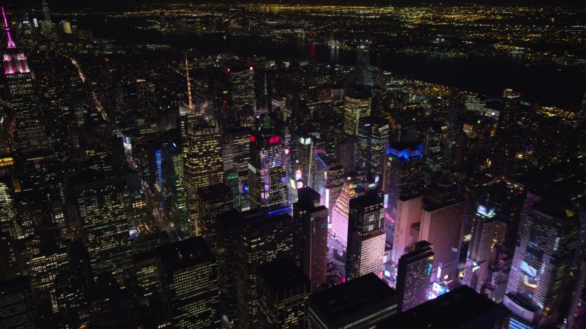 5.5K stock footage aerial video of circling the Bank of America Tower toward the glow of Times Square at Night, Midtown, NYC Aerial Stock Footage | AX122_115E