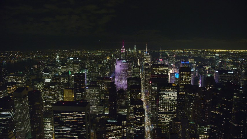 6K stock footage aerial video fly over Midtown toward Rockefeller Center at Night in NYC Aerial Stock Footage | AX122_135