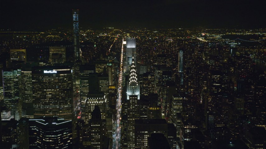 Approach the Chrysler Building by Lexington Avenue at Night in Midtown Aerial Stock Footage | AX122_157