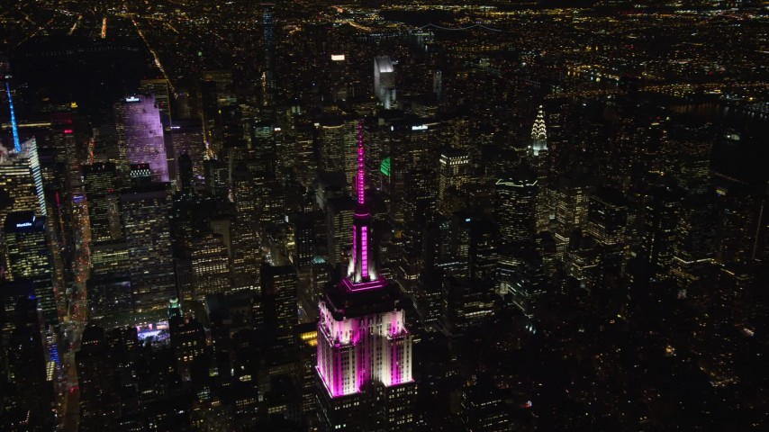 5.5K stock footage aerial video orbit the Empire State Building and zoom wider at Night, Midtown Manhattan NYC Aerial Stock Footage | AX122_167E