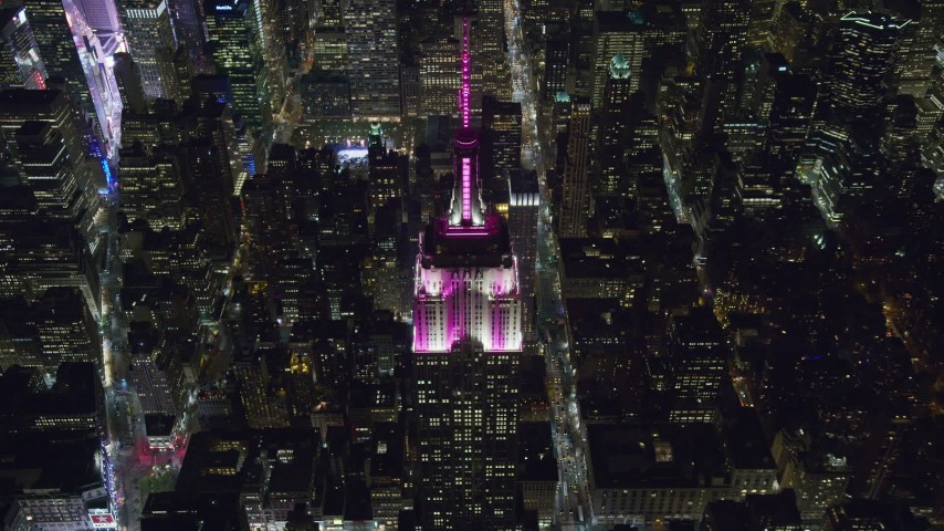 6K stock footage aerial video approach the historic Empire State Building at tilt to the spire at Night, Midtown, New York City Aerial Stock Footage | AX122_194