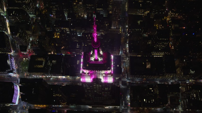 5.5K stock footage aerial video approach the historic Empire State Building at tilt to the spire at Night, Midtown, New York City Aerial Stock Footage | AX122_194E