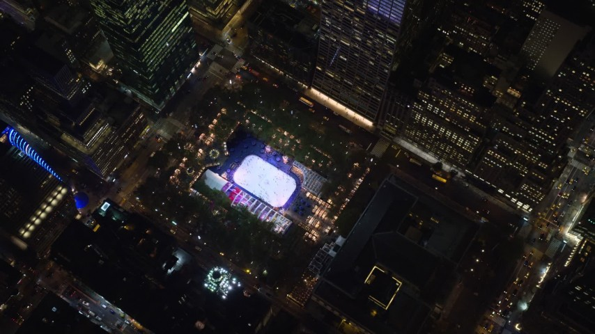 6K stock footage aerial video of a bird's eye of ice rink at Bryant Park at Night in Midtown, New York City Aerial Stock Footage | AX122_196