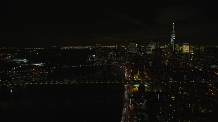 6K stock footage aerial video of approaching the Manhattan and Brooklyn Bridge in Lower Manhattan at Night in NYC Aerial Stock Footage | AX122_258