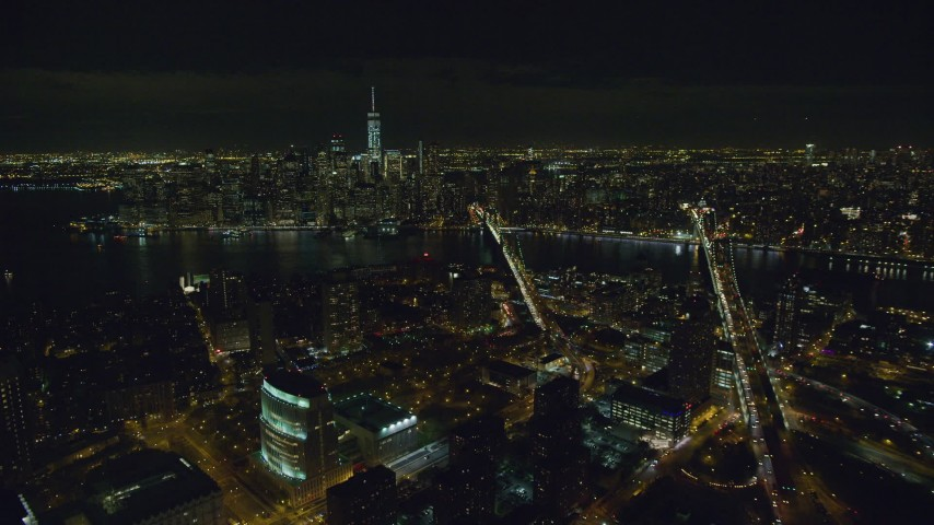 6K stock footage aerial video fly over Brooklyn to approach bridges over East River and Lower Manhattan at Night, NYC Aerial Stock Footage AX122_275 | Axiom Images
