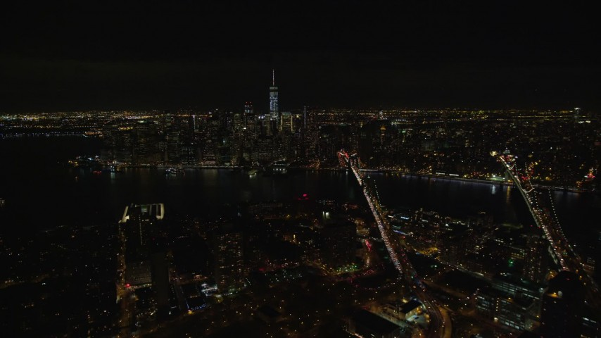 5.5K stock footage aerial video fly over Brooklyn to approach bridges over East River and Lower Manhattan at Night, NYC Aerial Stock Footage   AX122_275E