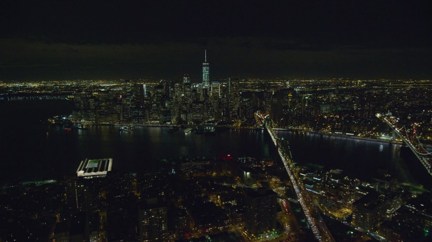 Approach Lower Manhattan from Brooklyn at Nighttime Aerial Stock Footage | AX122_277