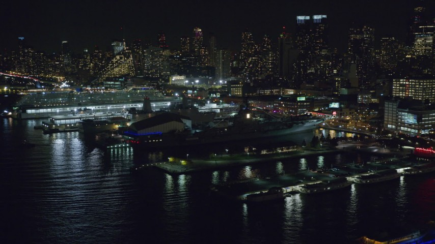 6K stock footage aerial video approach USS Intrepid in Hell's Kitchen at Night in Midtown, New York City Aerial Stock Footage | AX123_002