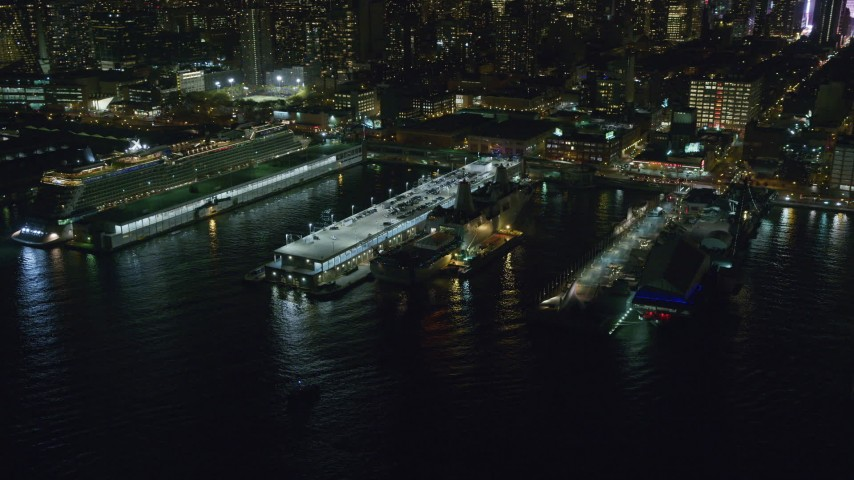 6K stock footage aerial video fly away from and orbit warships and a cruise ship in Hell's Kitchen docks at Night, Midtown, New York City Aerial Stock Footage | AX123_009