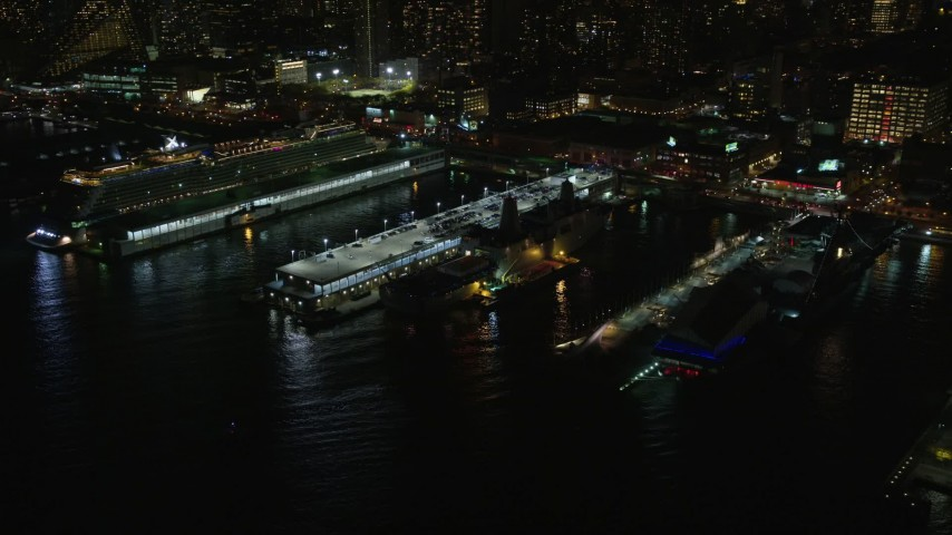 5.5K stock footage aerial video fly away from and orbit warships and a cruise ship in Hell's Kitchen docks at Night, Midtown, New York City Aerial Stock Footage   AX123_009E