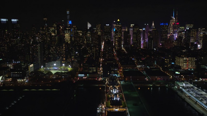 5.5K stock footage aerial video of Midtown skyscrapers seen from a cruise ship docked in Hell's Kitchen at Night, NYC Aerial Stock Footage | AX123_011E