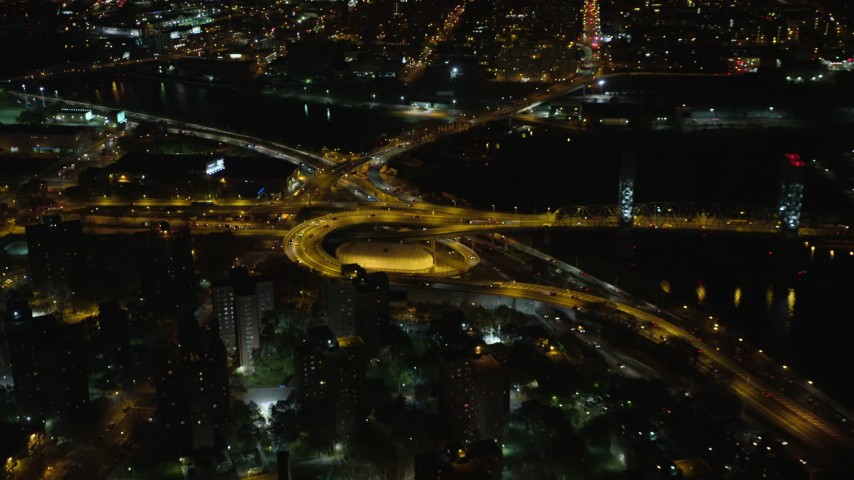 6K stock footage aerial video of riverfront freeway interchange by Robert F. Kennedy Bridge at Night, Harlem, New York City Aerial Stock Footage | AX123_031