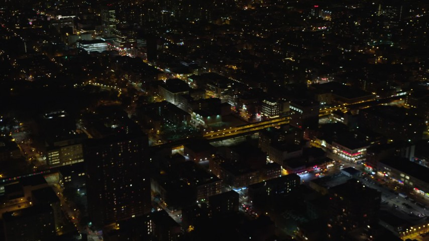 6K stock footage aerial video fly over apartment buildings by elevated rail tracks at Night in Harlem, New York City Aerial Stock Footage | AX123_032