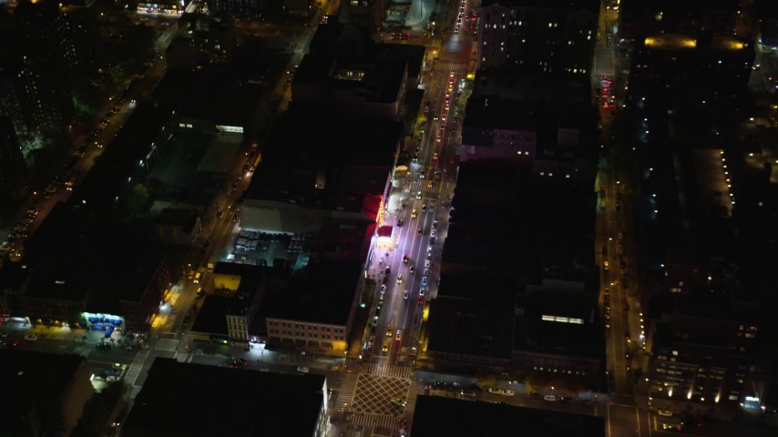 6K stock footage aerial video fly away from a Harlem shop on 125th Street at Night in NYC Aerial Stock Footage | AX123_038