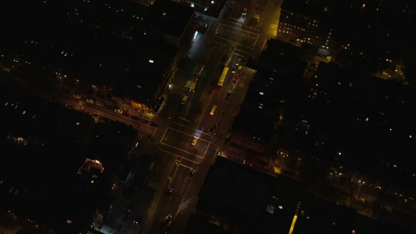 6K stock footage aerial video of a bird's eye view of a bus on a Harlem Street at Night in New York City Aerial Stock Footage | AX123_041
