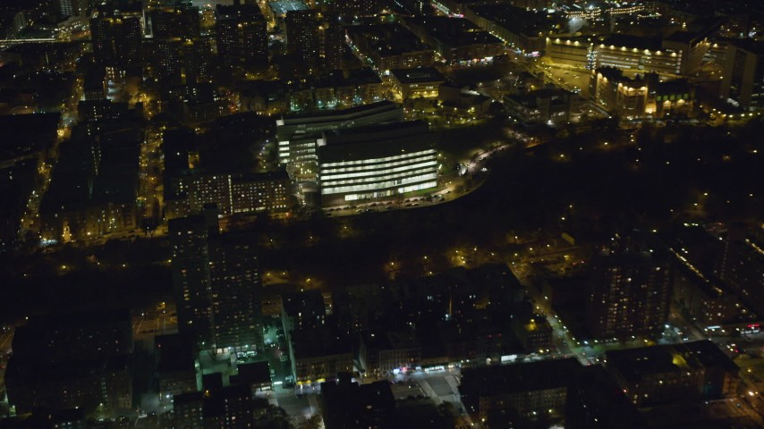 6K stock footage aerial video approach a modern Harlem office building at Night in NYC Aerial Stock Footage | AX123_043