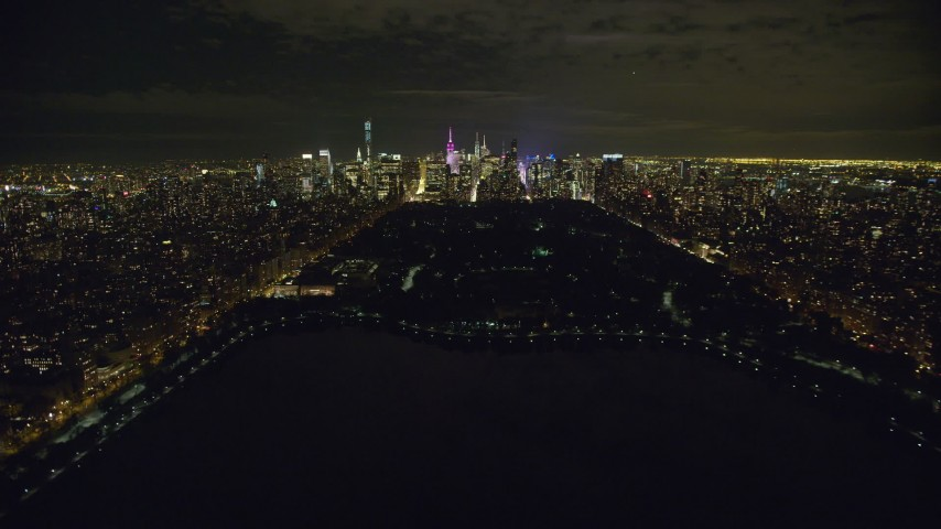 6K stock footage aerial video fly over reservoir in Central Park toward Midtown Manhattan at Night in New York City Aerial Stock Footage | AX123_053