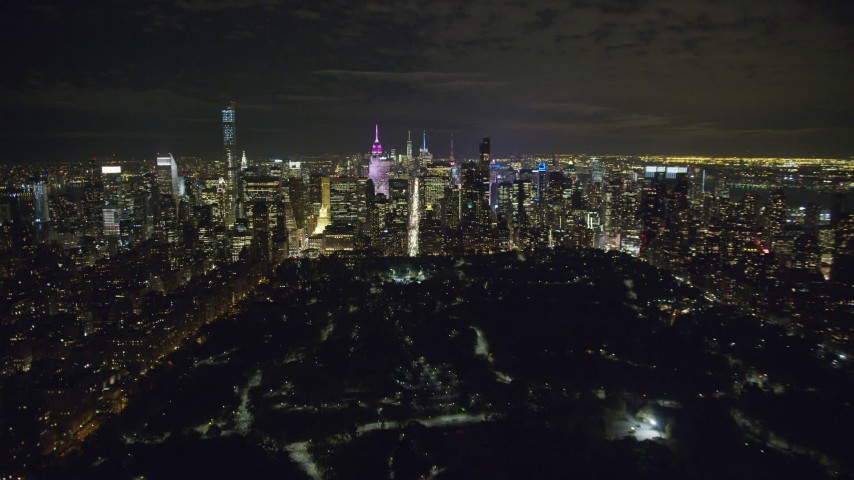 Approach Midtown at Night from Central Park in NYC Aerial Stock Footage AX123_056
