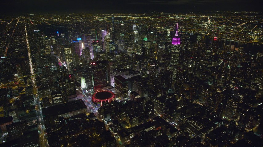 6K stock footage aerial video of Madison Square Garden and tall Midtown towers at Night in New York City Aerial Stock Footage | AX123_076