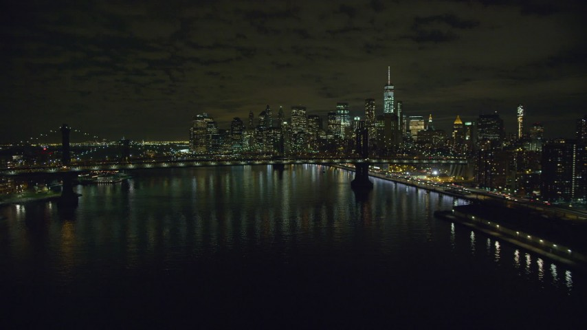 6K stock footage aerial video of an approach to the Manhattan Bridge and Lower Manhattan skyscrapers at Night in NYC Aerial Stock Footage | AX123_102