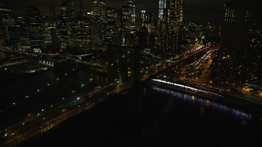 5.5K stock footage aerial video of flying toward the Lower Manhattan skyline and the Brooklyn Bridge at night in NYC Aerial Stock Footage   AX123_105E