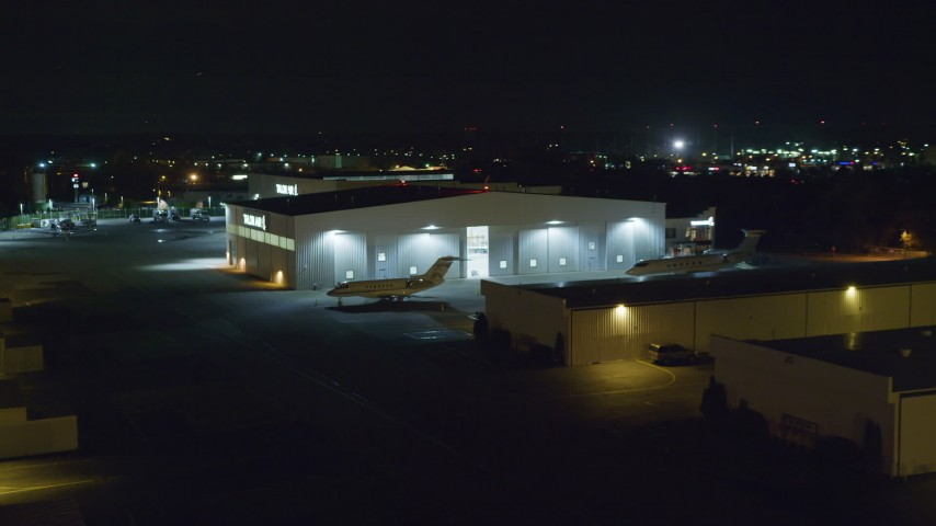 6K stock footage aerial video of civilian jets parked outside a hangar at Night at Republic Airport in Farmingdale, New York Aerial Stock Footage | AX123_191