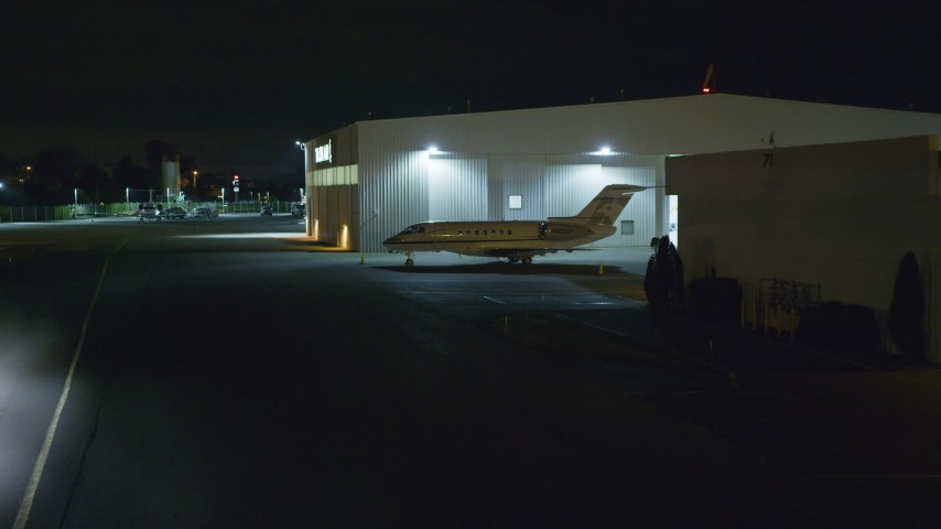 6K stock footage aerial video approach civilian jet parked at Republic Airport at Night in Farmingdale, New York Aerial Stock Footage AX123_192 | Axiom Images