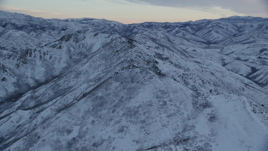 6K stock footage aerial video orbit snowy ridge of Wasatch Range at Sunrise in Utah Aerial Stock Footage | AX124_025