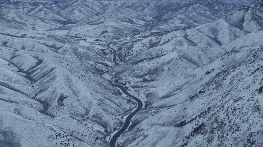 6K stock footage aerial video of a mountain road through snowy Wasatch Range at Sunrise in Utah Aerial Stock Footage | AX124_028