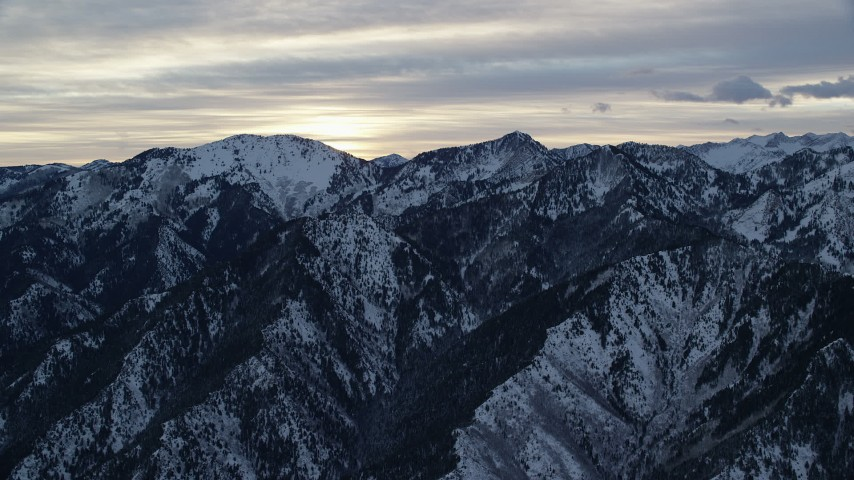 Approach Snowy Mountains in Wasatch Range at Sunrise in Utah Aerial Stock Footage | AX124_033