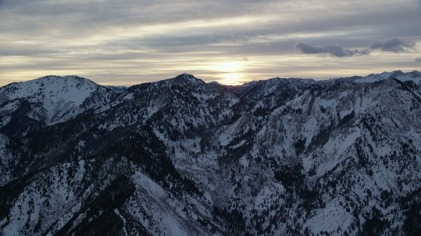6K stock footage aerial video of the sunrise over snowy winter Wasatch Range mountains in Utah Aerial Stock Footage | AX124_039