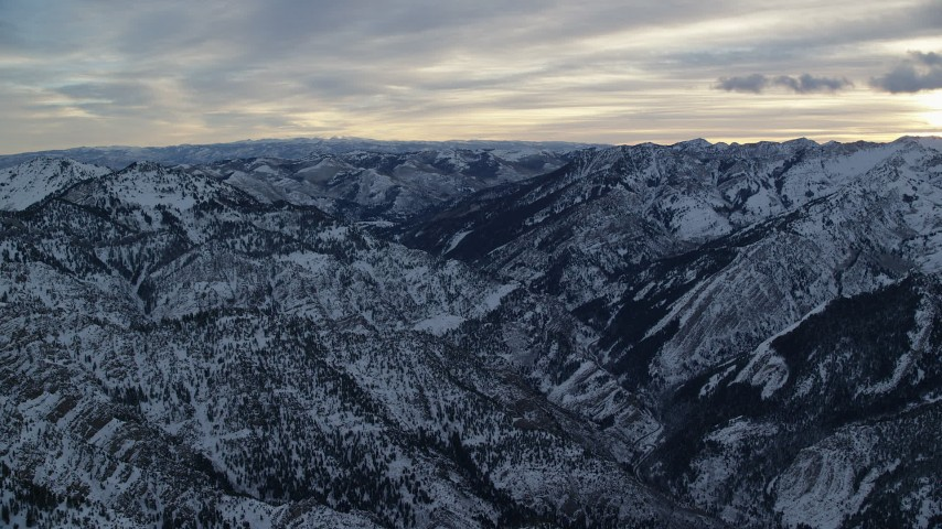 Snowy Wasatch Range Mountains in Winter at Sunrise in Utah Aerial Stock Footage   AX124_051
