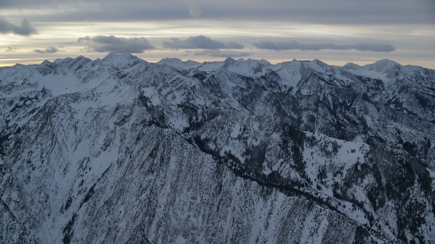 6K stock footage aerial video approach snowy Wasatch Range mountains in winter at sunrise, Utah Aerial Stock Footage | AX124_054
