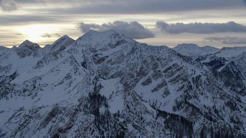 Wasatch Range Mountain Peaks with Winter Snow at Sunrise in Utah Aerial Stock Footage   AX124_058