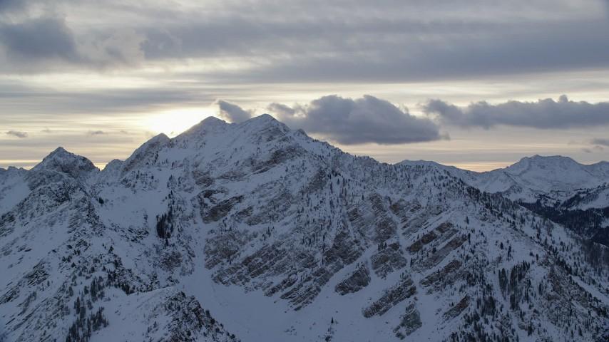 6K stock footage aerial video of sunrise behind snowy Wasatch Range Peak in winter, Utah Aerial Stock Footage | AX124_060