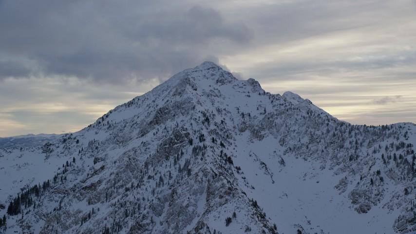 6K stock footage aerial video orbit peak with winter snow in Wasatch Range at sunrise in Utah Aerial Stock Footage | AX124_063