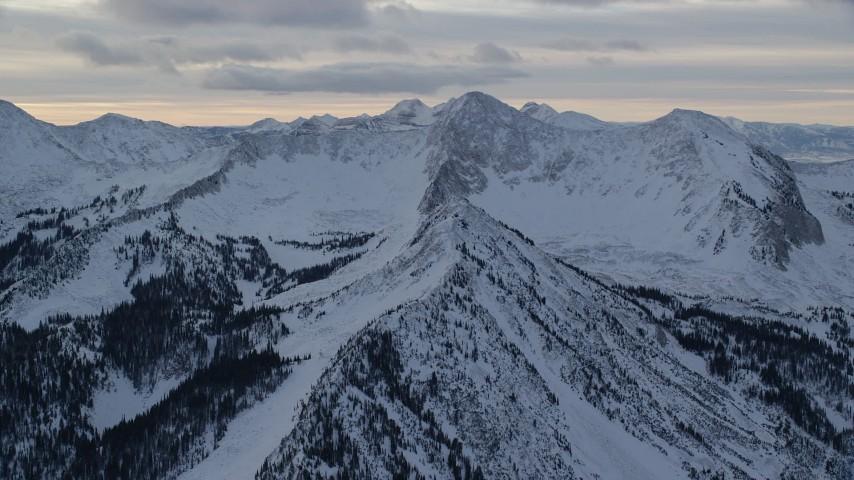 6K stock footage aerial video orbit snowy Wasatch Range mountain ridges in winter at sunrise in Utah Aerial Stock Footage | AX124_067