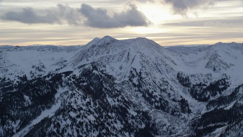 Orbiting Snowy Peak in Winter at Sunrise in Wasatch Range, Utah Aerial Stock Footage | AX124_068