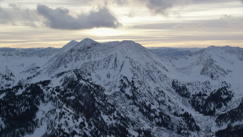 6K stock footage aerial video orbit a snowy peak at sunrise in the Wasatch Range of Utah Aerial Stock Footage | AX124_069