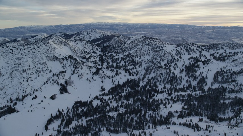 6K stock footage aerial video approach Wasatch Range snow mountains at winter sunrise in Utah Aerial Stock Footage | AX124_075
