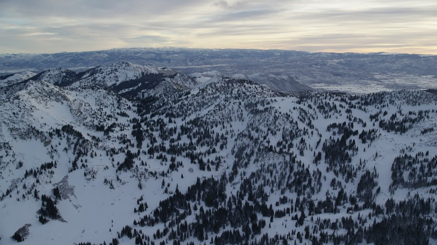 6K stock footage aerial video pan across snow mountains at sunrise in Wasatch Range, Utah Aerial Stock Footage | AX124_076