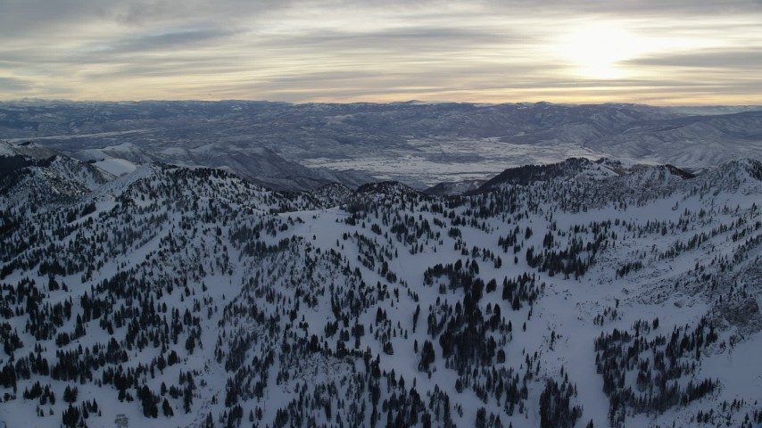 Sunrise seen while Orbiting Wasatch Range Snow Mountains in Utah Aerial Stock Footage   AX124_077