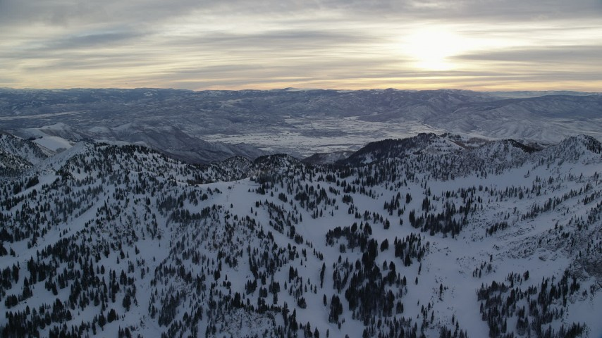 Sunrise seen while Orbiting Wasatch Range Snow Mountains in Utah Aerial Stock Footage | AX124_077