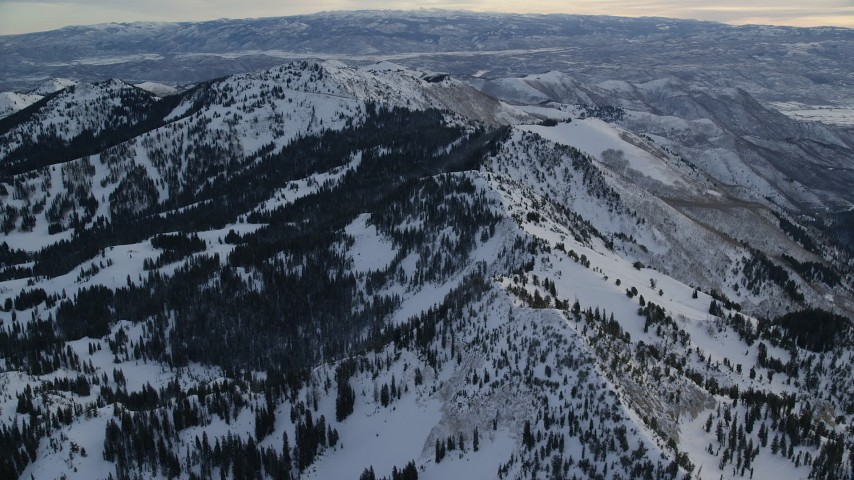 Fly Over Snowy Mountain Ridge at Sunrise in Wasatch Range, Utah Aerial Stock Footage   AX124_080