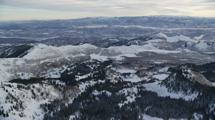 6K stock footage aerial video fly over hilly valley with winter snow toward mountain ridge at sunrise, Wasatch Range, Utah Aerial Stock Footage | AX124_085