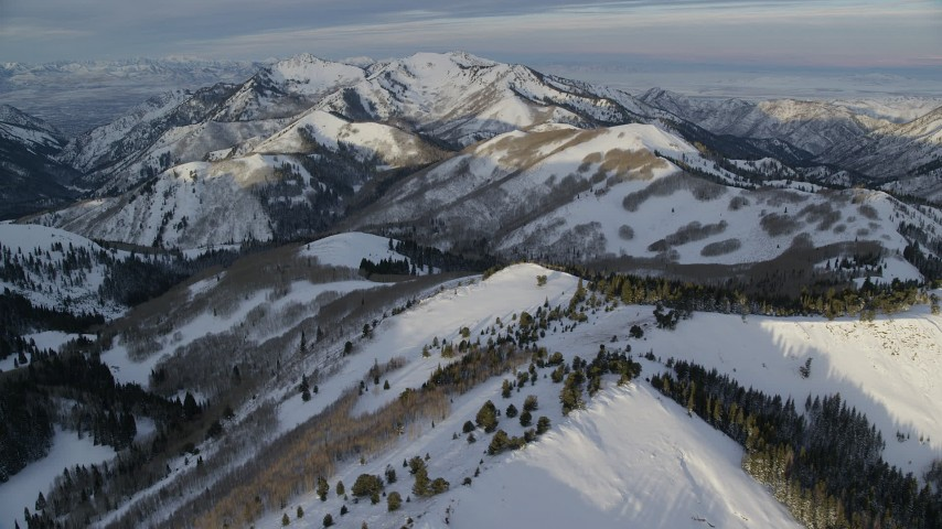 Mountains with Winter Snow at Sunrise in the Wasatch Range, Utah Aerial Stock Footage   AX124_101